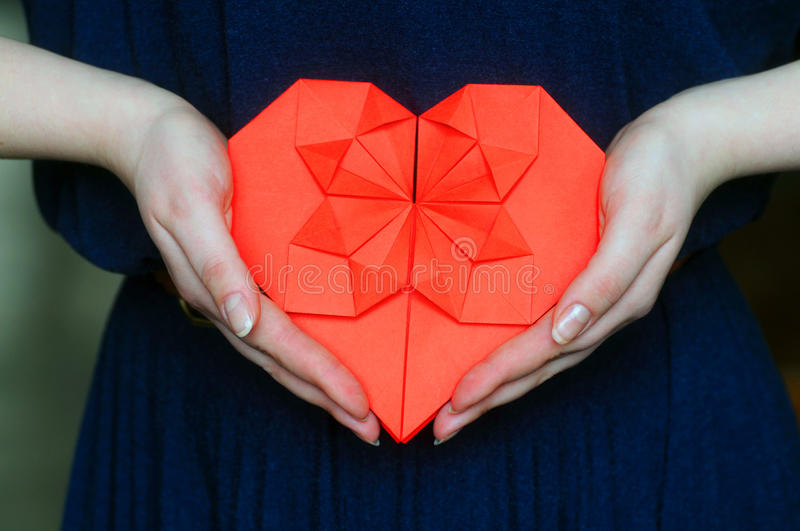 Red origami heart in girl`s hands stock image
