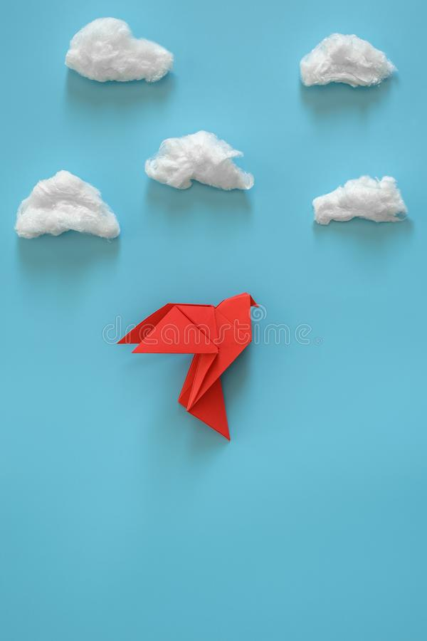 Red origami paper dove on a blue background among the white clouds royalty free stock image