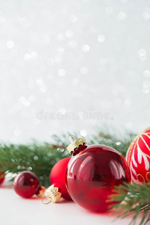 Red ornaments and xmas tree on glitter holiday background. Merry christmas card. Winter theme. Happy New Year. Space for text royalty free stock images