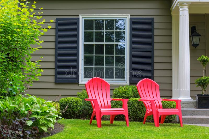 Red Outdoor patio Chairs on Front Yard green Lawn. Red outdoor chairs on green grass lawn of house manicured front yard stock photography