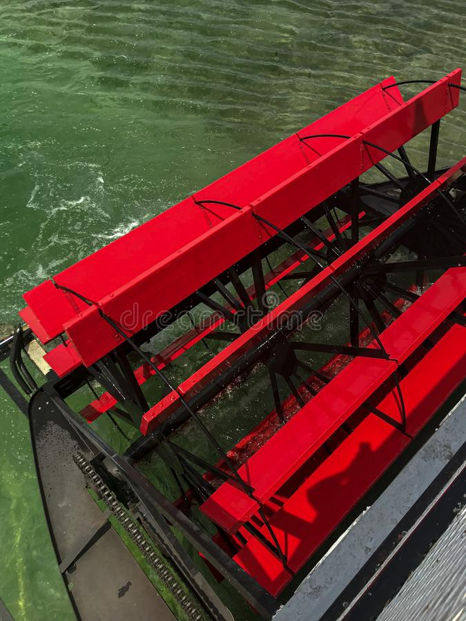 Red Paddlewheel on a Steamboat. A red paddlewheel on a steamboat. Red wood boards run by steam to make the boat move. Fresh water lake stock images