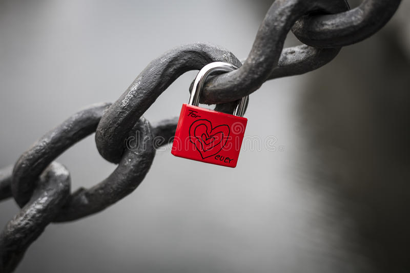 Red padlock hanging on a big chain royalty free stock photography