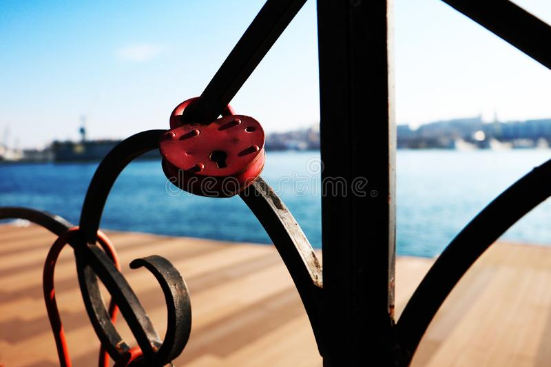 Red heart padlock attached to iron fence near the sea stock photography