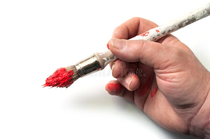 red paint on brush in hand on white background stock photo