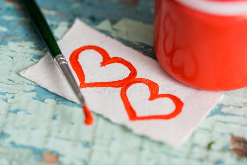 Red paint gouache in a jar, brush. painted two hearts on a scrap of paper. on a textured old cracked blue green background on a wo. Oden table. Place for your stock image
