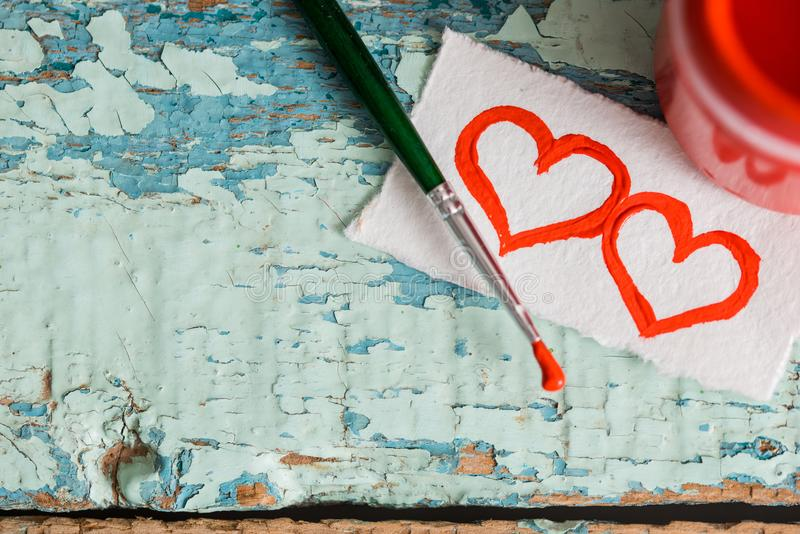 Red paint gouache in a jar, brush. painted two hearts on a scrap of paper. on a textured old cracked blue green background on a wo. Oden table. Place for your stock photos