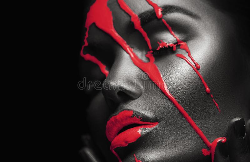 Red Paint smudges drips from African American woman face, lips, eyes. Lipgloss dripping from sexy lips. Liquid drops on beautiful model girl`s mouth, black royalty free stock photos