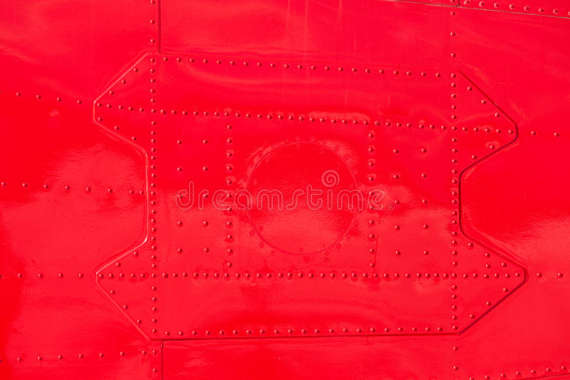 Red painted riveted metal airplane fuselage skin. Bright red painted riveted metal sheet skin of airplane fuselage background texture pattern royalty free stock photos