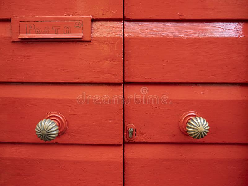 Red painted wood door with a mail box. Inside royalty free stock image