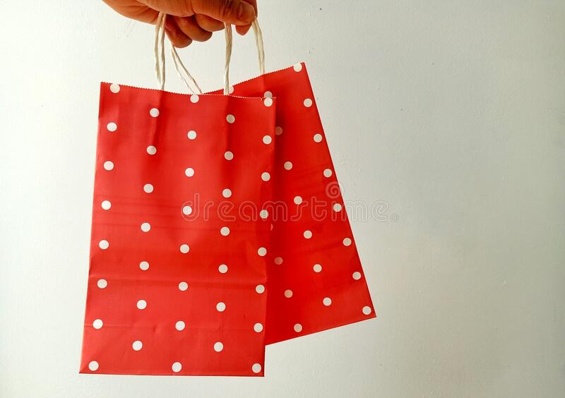 2 red paper bags with white stripes, background wall,. White royalty free stock photos