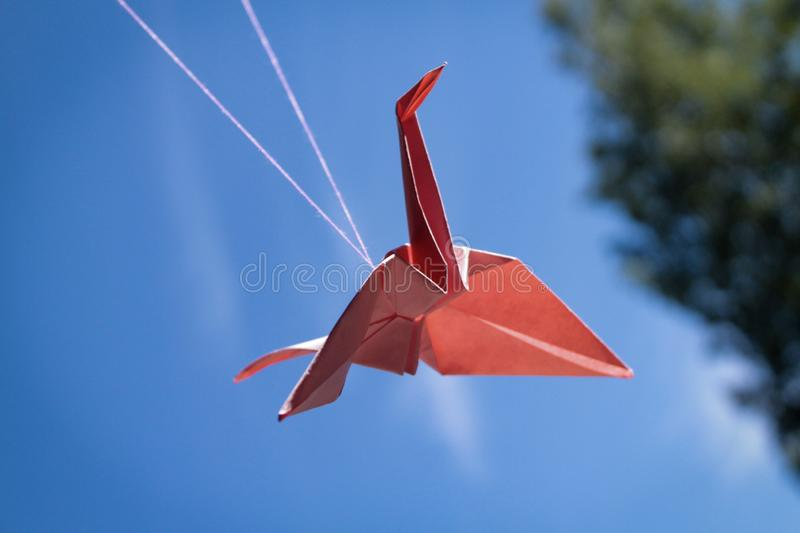 Red paper bird origami crane on sky royalty free stock photo