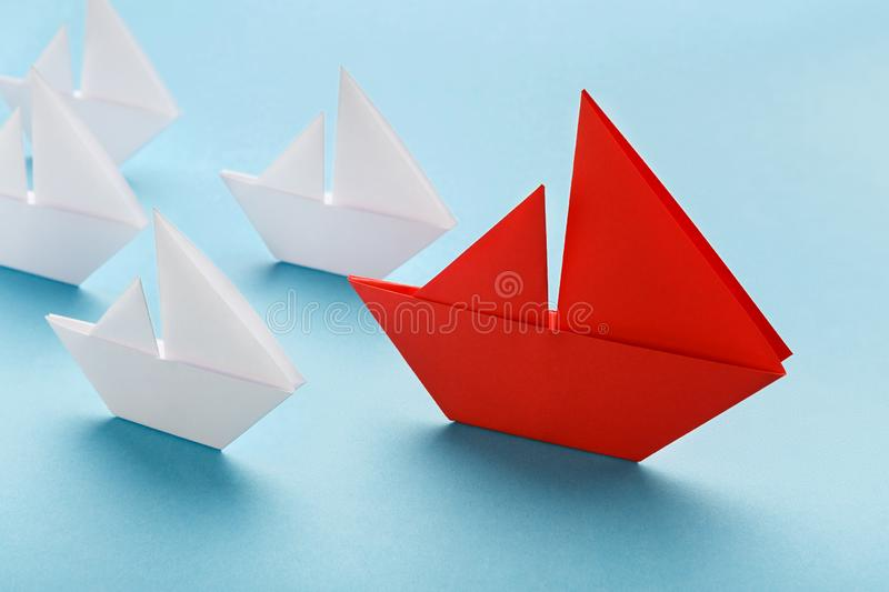Red paper boat leading white ships, panorama. Influencer concept. One red boat guiding small white ships on blue background stock photos