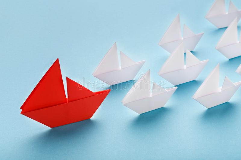Red paper boat leading white ships, panorama. Opinion Leader, influencer concept. One red boat leading small white ships on blue background royalty free stock photo