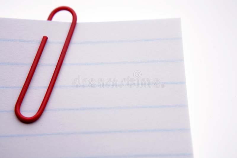 Red paper clip on papers. Closeup of a red, plastic paper clip on blank, lined notepaper stock images