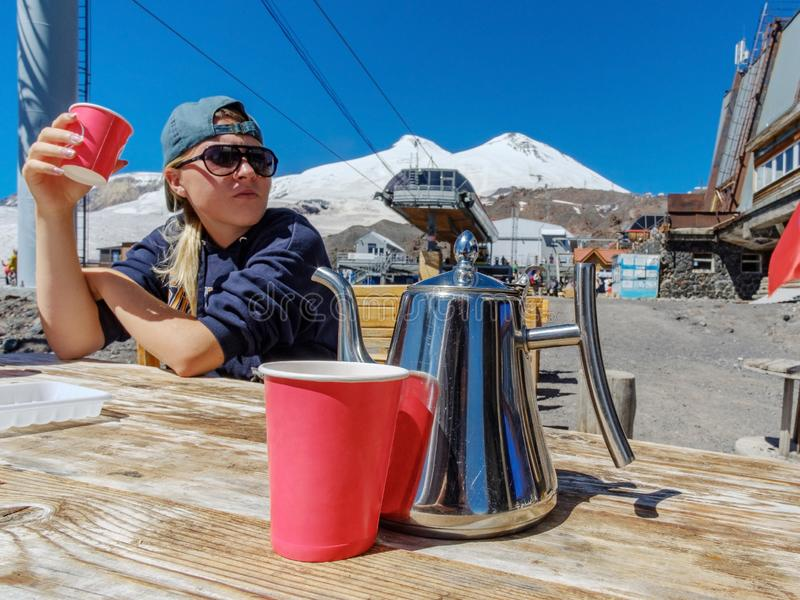 A red paper cup and a metal coffee pot on a wooden table and a girl in sunglasses drinking coffee in the mountains stock image