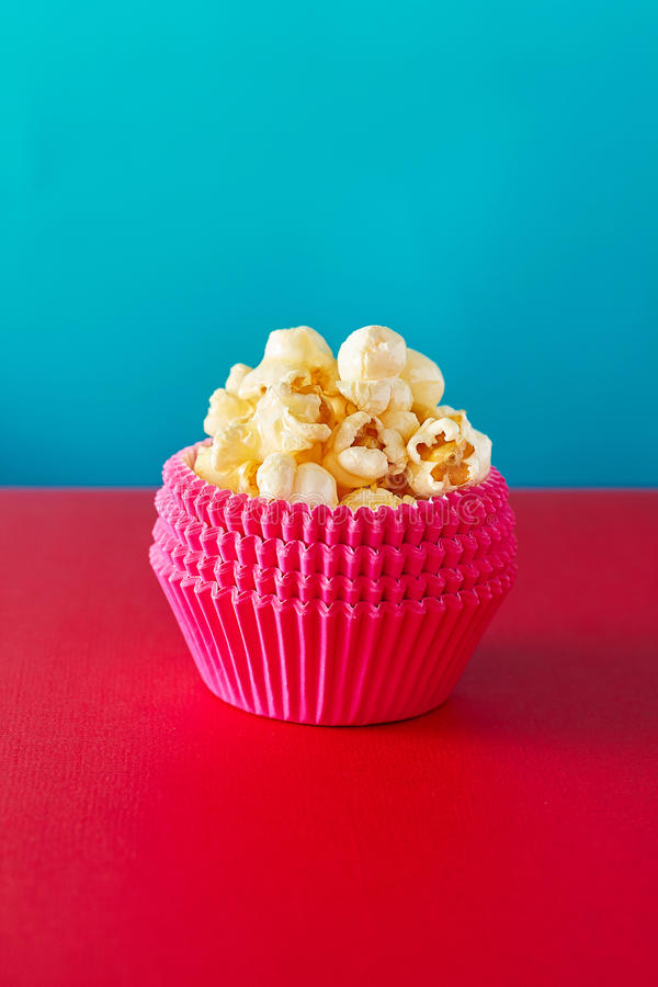Red paper cup with popcorn against vibrant background. stock photography