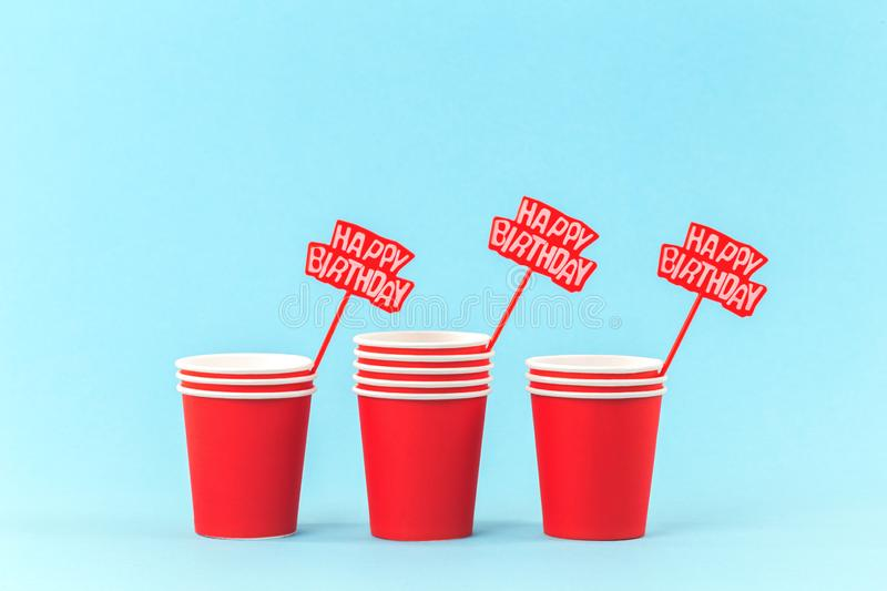 Red paper cups and happy birthday spikes royalty free stock photography