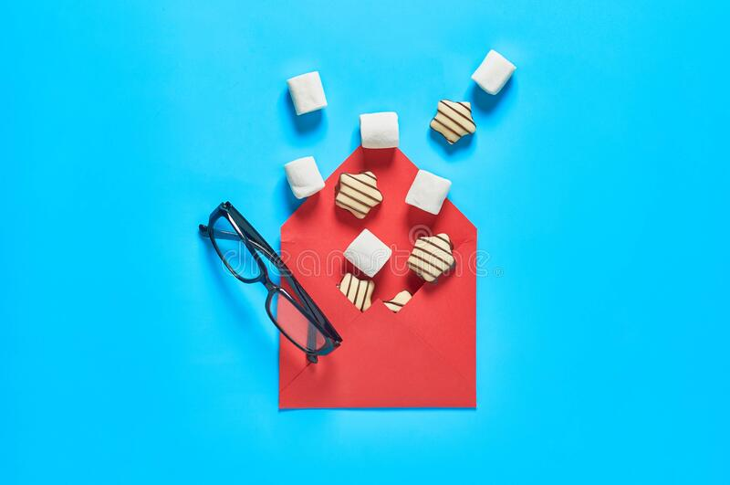 Red paper envelope with scattered sweets, striped candies, cylindrical marshmallows near optical glasses in black plastic frame stock image