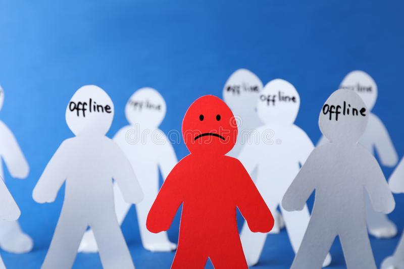 Red paper figure among white ones on color background. Solitude concept stock photo