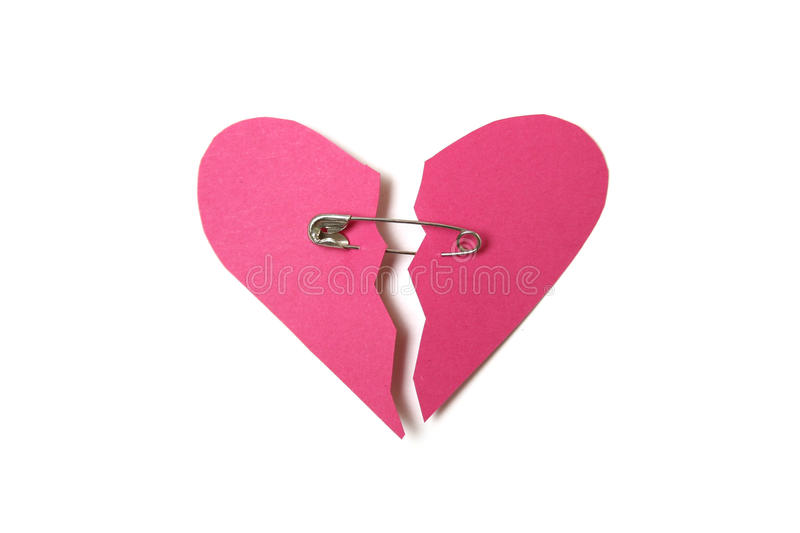 Red paper heart. Torn in half secured with safety pin on white background royalty free stock photo