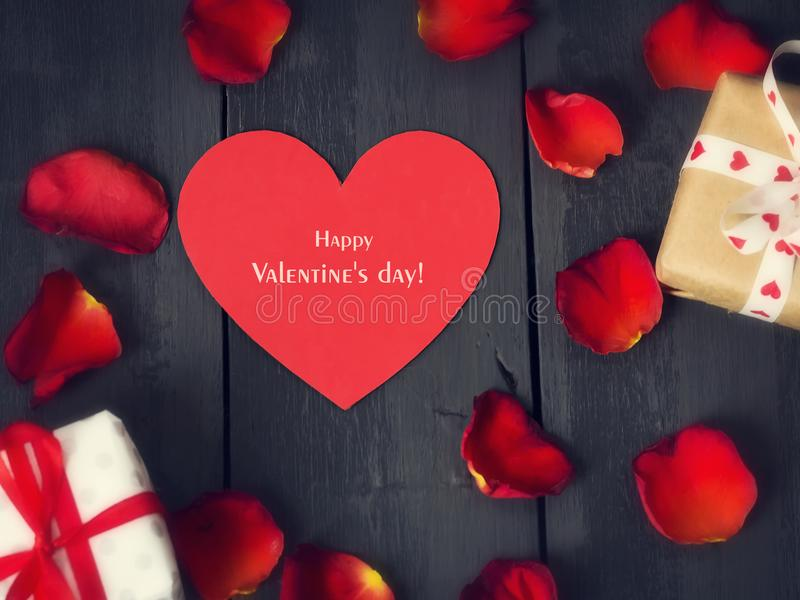 Red paper heart with rose petals and gifts on a dark wooden background. St. Valentine`s Day. stock image