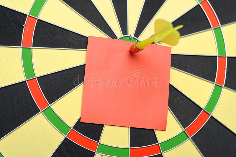 Red Paper Note With Dart Arrow. On dartboard. You can put your message on the paper stock image