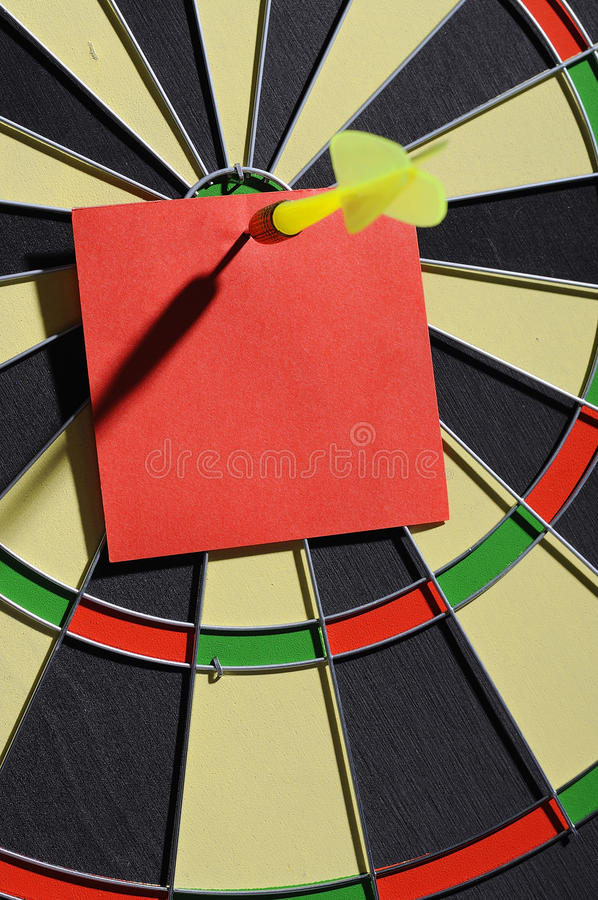 Red Paper Note With Dart Arrow. On dartboard. You can put your message on the paper royalty free stock photography