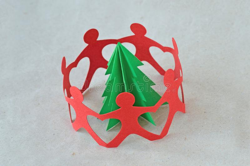 Red paper people in a circle around a tree on recycled paper background - Ecology concept stock photo