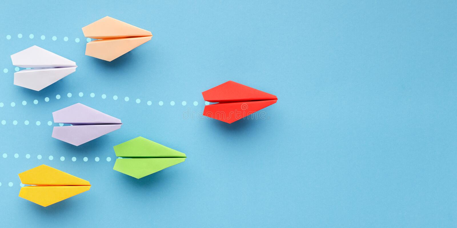 Red paper plane leading another ones, leadership concept. Opinion leadership concept. Red paper plane leading another colorful ones, influencing the crowd, blue royalty free stock photography