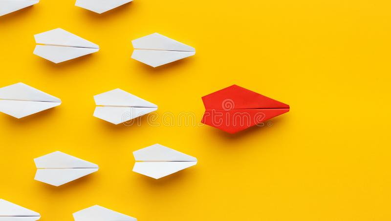 Red paper plane leading another ones, leadership concept. Opinion leadership. Red paper plane leading another colorful ones, influencing the crowd, yellow royalty free stock photos