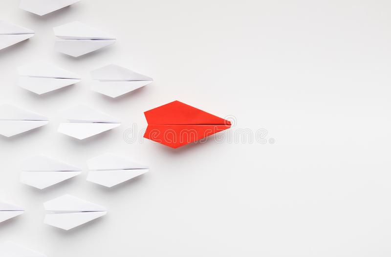 Red paper plane leading another ones, leadership concept. Opinion leadership concept. Red paper plane leading another ones, influencing the crowd, white stock photo