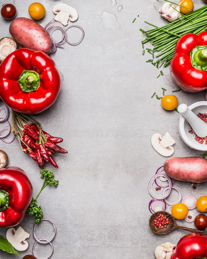Red paprika and diverse vegetables and cooking ingredients on gray stone background, top view, frame, vertical stock images