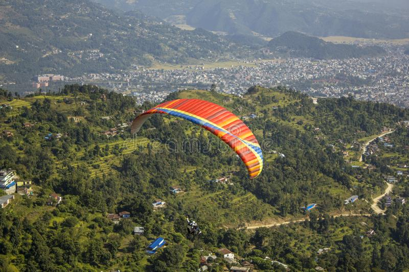 Red parachute with a blue stripe of a paraglider flying in tandem against a background of green mountains and a city in the valley stock photos