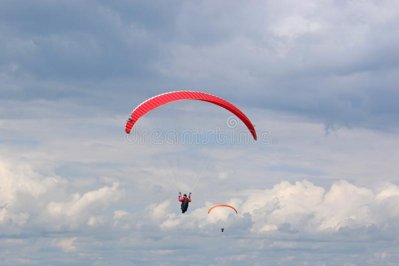 Red paraglider in a blue sky stock photo