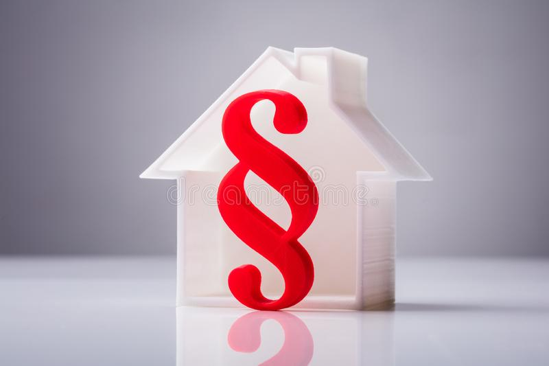 Red Paragraph Symbol In Front Of House Model. On Reflective Background stock photo
