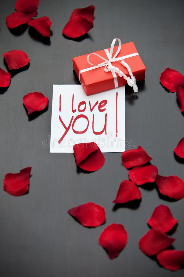 Red parcel with a white ribbon and an I-love-you-note on a black table, surrounded by red rose petals. royalty free stock images