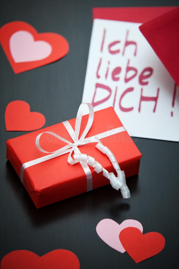 Red parcel with a white ribbon and an I-love-you-note in German with a red envelope on a black table. stock image