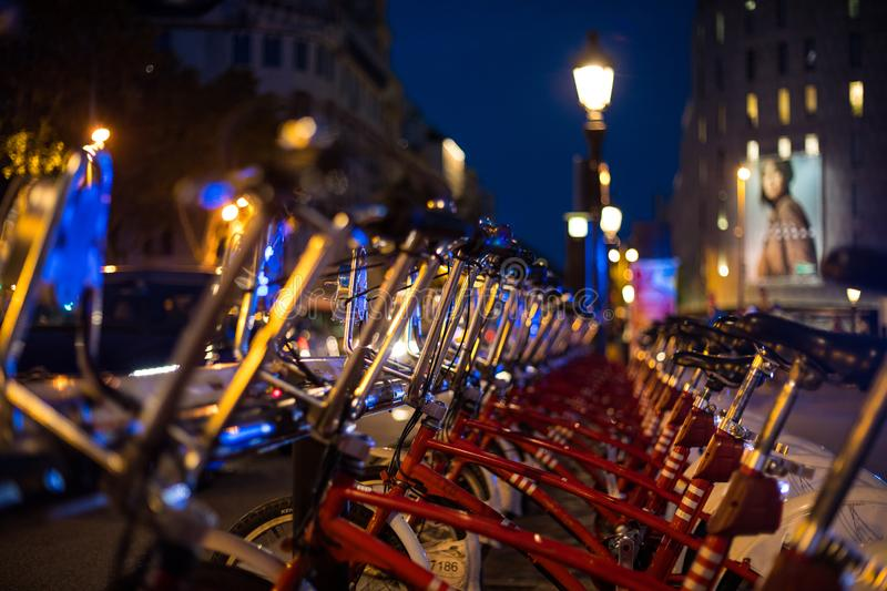 Red parked rental bikes at night perspective shot. From Barcelona stock image