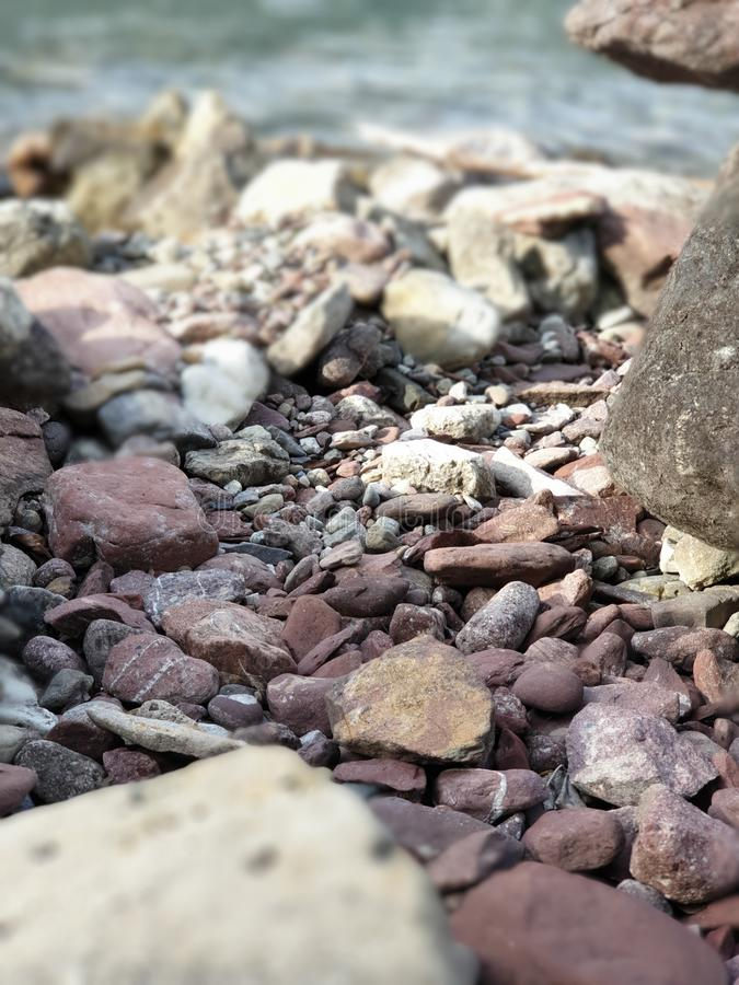 red and colored pebbles at the blue lake stock photography