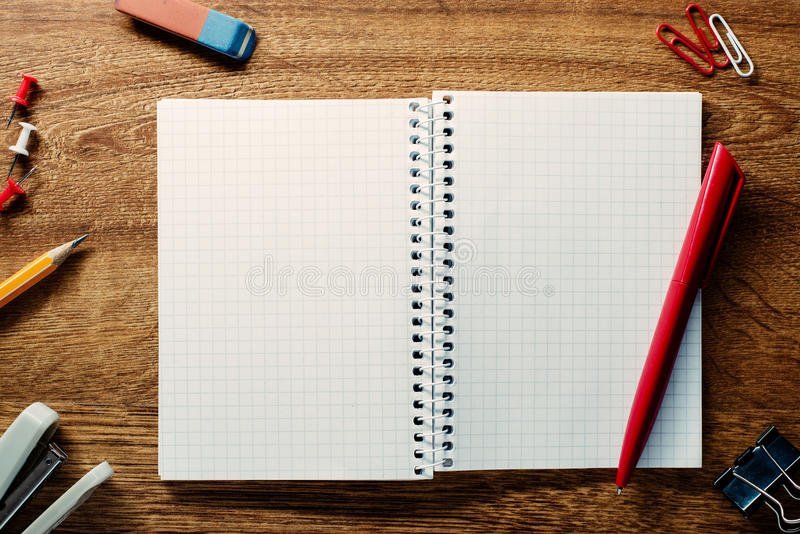 Red pen ready for writing on an open notebook stock photo