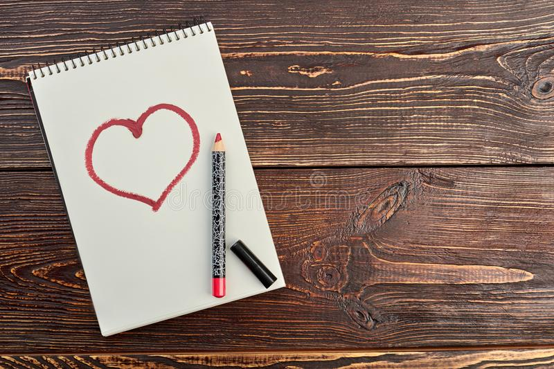 Red pencil and a drawn heart. Paper notebook with image of red heart, pencil and copy space. Beauty and love royalty free stock photos