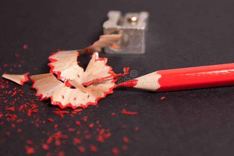 Red pencil with pencil shavings and pencil sharpener up close royalty free stock photos