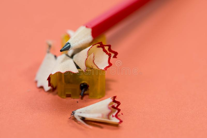 Red pencil on sharpening waste and plastic sharpener close up macro shot royalty free stock photo