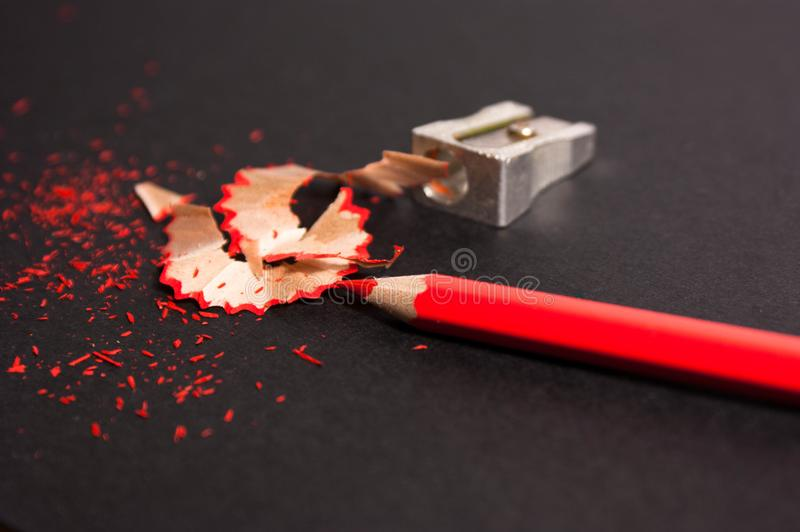 Red pencil with pencil shavings and pencil sharpener up close royalty free stock photo