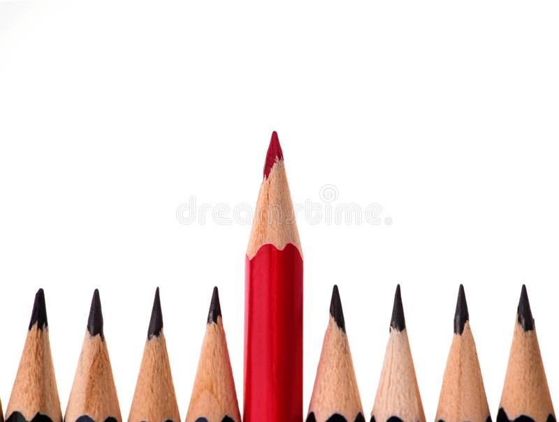 Red pencil standing out from crowd of plenty identical black fellows on white background. business success concept stock photos