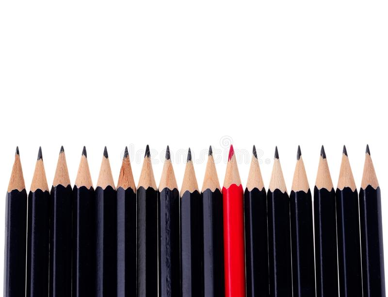 Red pencil standing out from crowd of plenty identical black fellows on white background. business success concept stock image