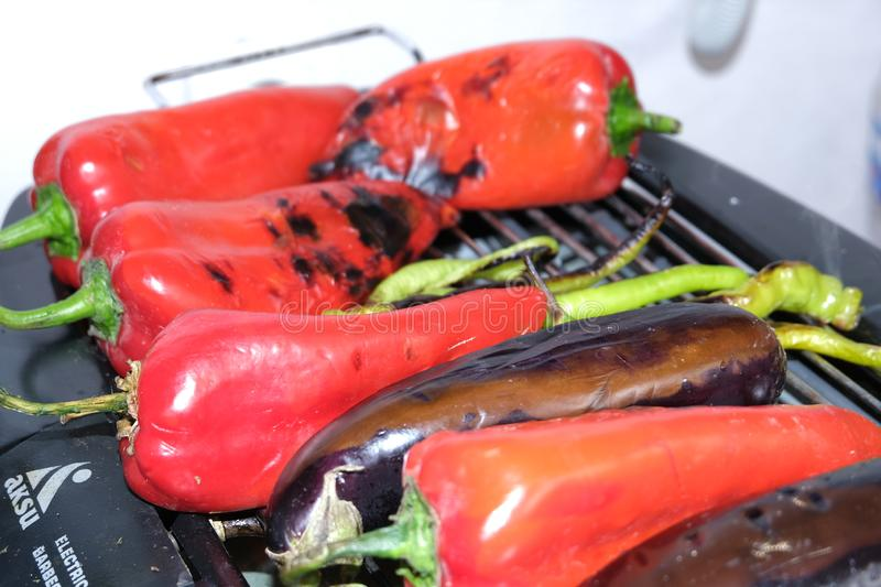 Red Pepper, Aubergine on barbecue grill on hot charcoal and fire. Preparing healthy food on holiday. Cooking vegetables on flames royalty free stock photos