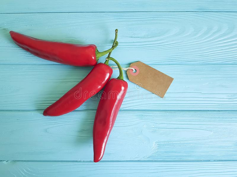 Red pepper on a blue wooden background spice tag. Red pepper a blue wooden background tag spice stock photos