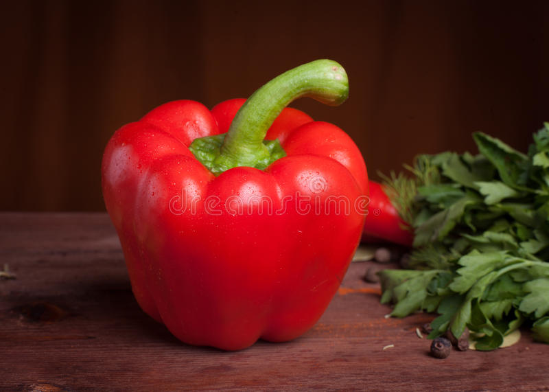 Red pepper on dark wood background with herbs. And spices stock photography