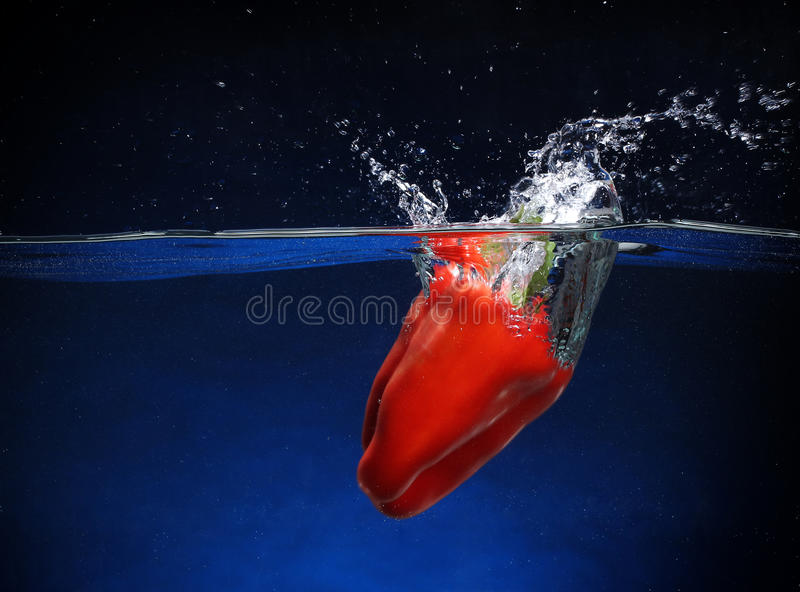 Red pepper falling into water